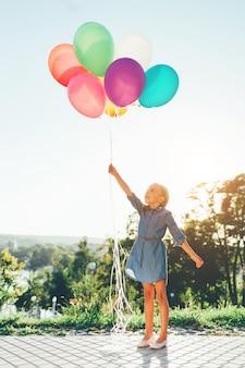 Niña sosteniendo globos de colores que se extiende hacia el cielo y soñando