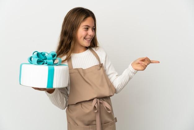Niña sosteniendo un gran pastel sobre fondo blanco aislado apuntando con el dedo hacia el lado y presentando un producto