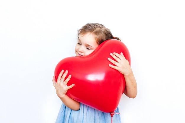 Niña sosteniendo un hermoso globo rojo en forma de corazón para un regalo para el día de san valentín, los amantes, el día de san valentín, la familia y el corazón