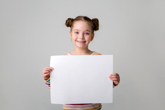 Niña sosteniendo una hoja blanca. niña linda con una hoja de papel blanco. fondo azul. espacio para texto. una niña sostiene un trozo de papel vacío.