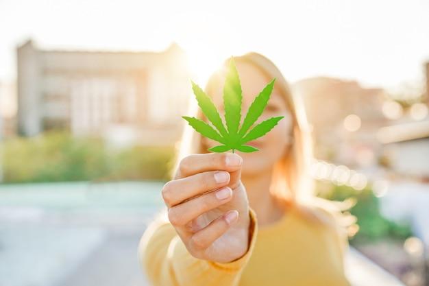 Niña sosteniendo hojas de marihuana con luz solar en segundo plano - medicina de cannabis, estilo de vida saludable y concepto de ecología - enfoque en la mano