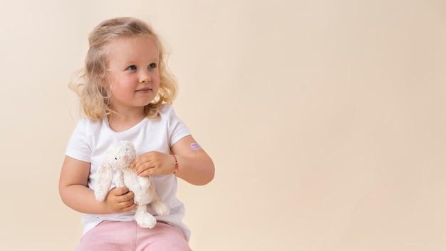 Niña sosteniendo un juguete después de recibir una vacuna