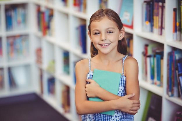 Niña sosteniendo un libro en la biblioteca