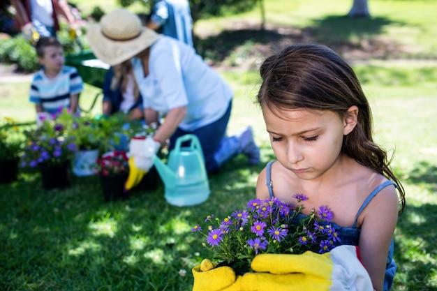 Niña sosteniendo una maceta mientras jardinería con familia