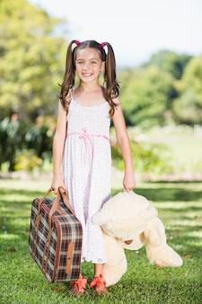 Niña sosteniendo una maleta y oso de peluche