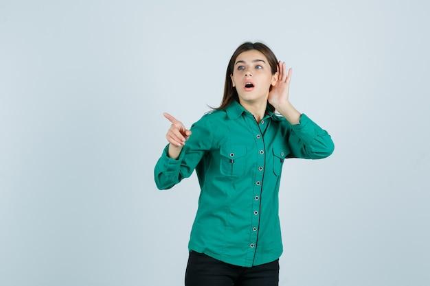 Niña sosteniendo la mano cerca de la oreja para escuchar algo, apuntando hacia afuera en blusa verde, pantalón negro y mirando enfocado. vista frontal.