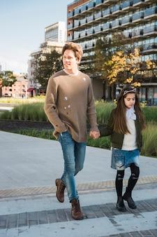 Niña sosteniendo la mano de su padre mientras camina sobre el pavimento