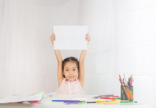 Niña está sosteniendo en las manos un papel vacío con espacio de copia, concepto de dibujo kid
