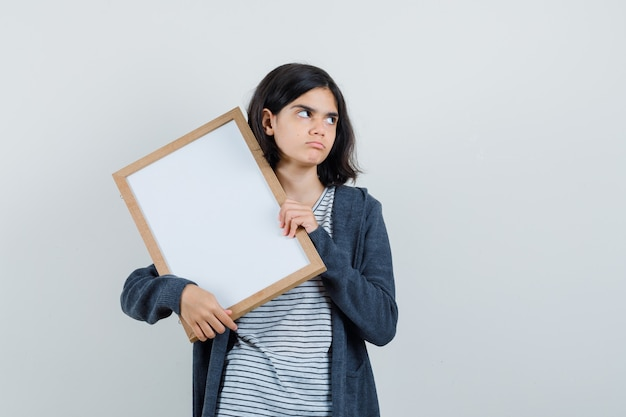 Niña sosteniendo marco vacío en camiseta, chaqueta y mirando pensativo.