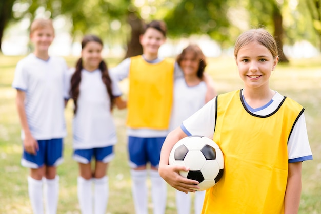 Niña sosteniendo una pelota de fútbol junto a sus compañeros de equipo