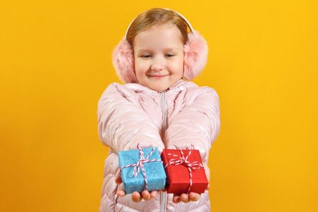 Niña sosteniendo pequeñas cajas con regalos.