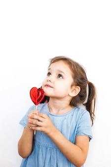 Niña sosteniendo una piruleta en forma de corazón, amantes, día de san valentín, familia y corazón