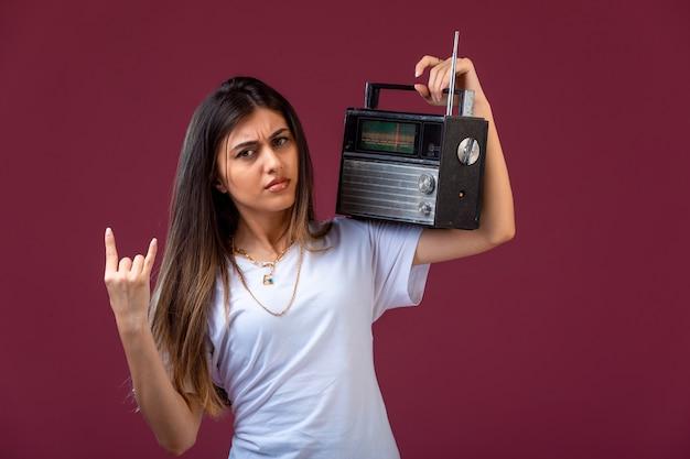 Niña sosteniendo una radio vintage en su hombro y parece dedicada.