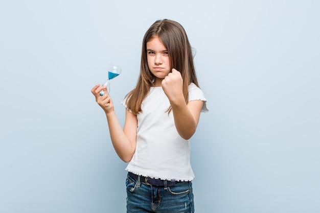 Niña sosteniendo un reloj de arena mostrando el puño a la cámara, expresión facial agresiva