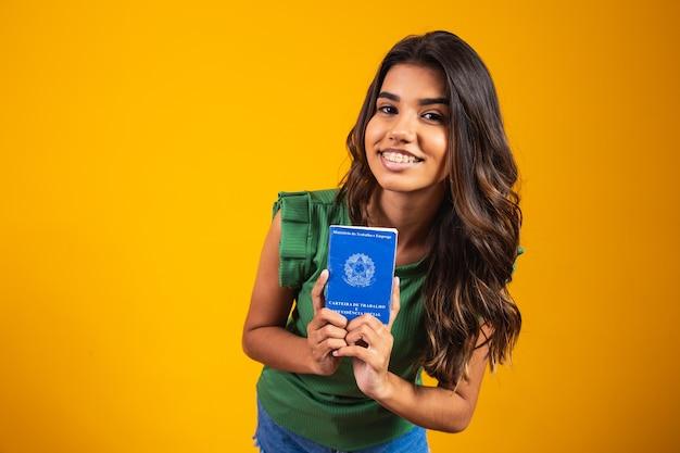 Niña sosteniendo la tarjeta de trabajo brasileña