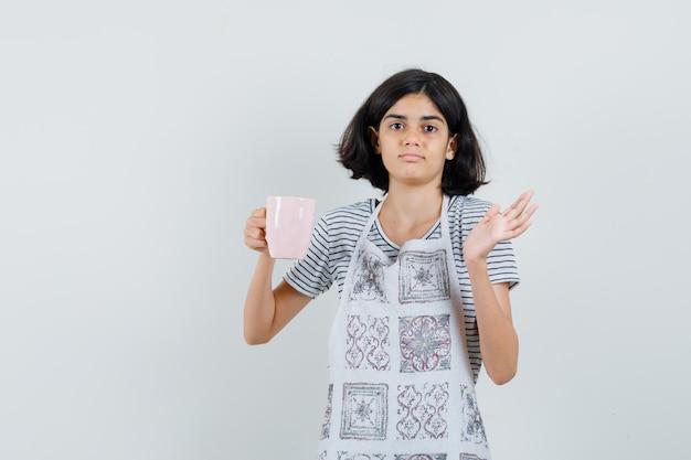 Niña sosteniendo una taza de bebida en camiseta, delantal y mirando confundido.