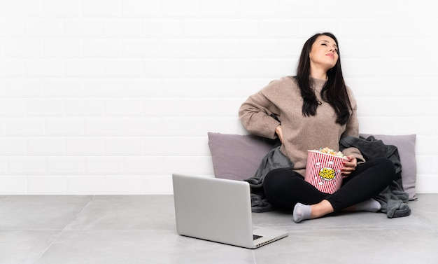 Niña sosteniendo un tazón de palomitas de maíz y mostrando una película en una computadora portátil que sufre de dolor de espalda por haber hecho un esfuerzo