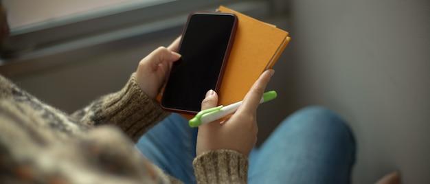 Una niña sosteniendo el teléfono inteligente y el libro de agenda mientras está sentado en la esquina de lectura junto a la ventana