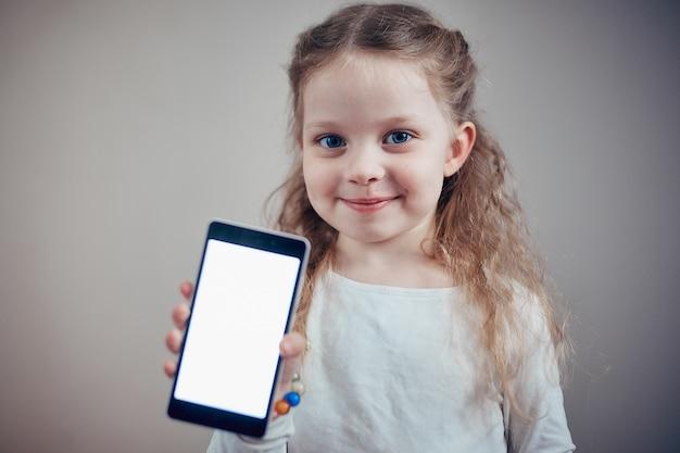 Niña sosteniendo un teléfono inteligente con una pantalla blanca
