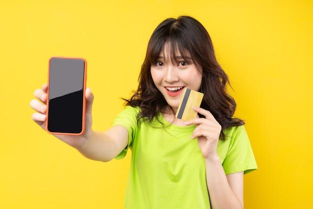 Niña sosteniendo teléfono y tarjeta de crédito con expresión alegre