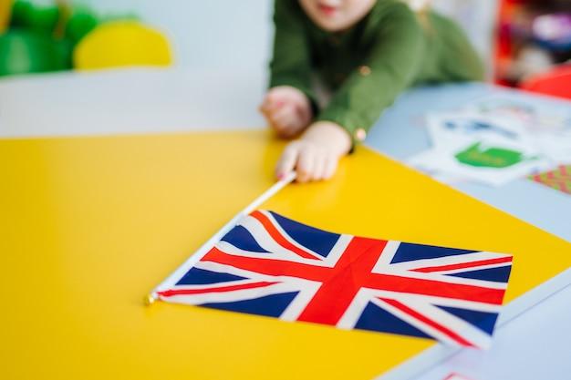 Niña sostiene la bandera de union jack. bandera británica en la vista frontal.