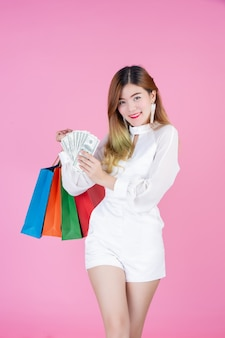 La niña sostiene un bolso de compras de moda y tiene una tarjeta de dólar.