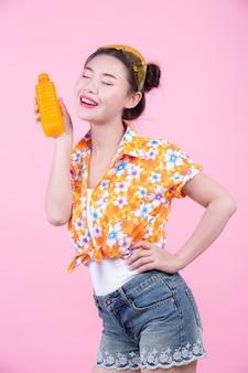 La niña sostiene una botella de jugo de naranja sobre un fondo rosa.