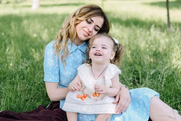 Niña sostiene cerezas con su madre afuera en un día de verano