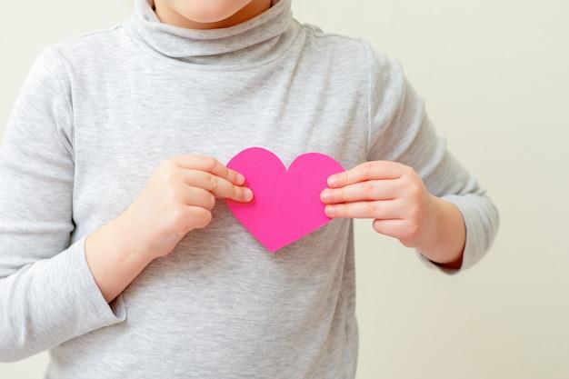 La niña sostiene el corazón de color rosa.