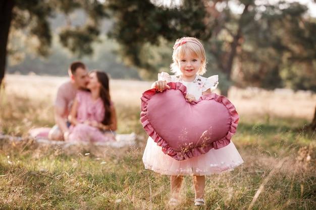 Niña sostiene un gran corazón rosa en el parque de verano mientras los padres se abrazan en el fondo