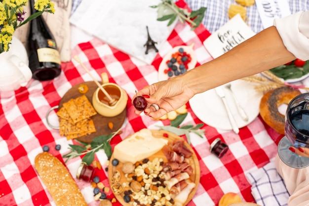 Niña sostiene jugosas cerezas maduras en su mano contra el fondo de una manta de picnic con comida