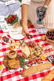 Niña sostiene jugosas cerezas maduras en su mano sobre una manta de picnic a cuadros