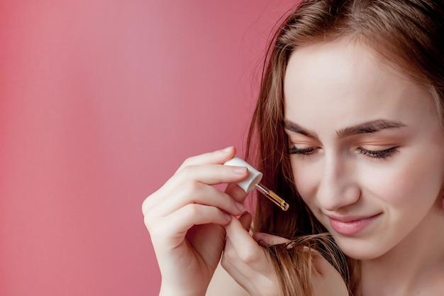 La niña sostiene en la mano las puntas de su cabello y su mano derecha les aplica aceite amarillo.