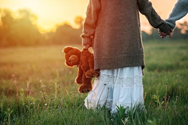 Niña sostiene un oso de peluche en la mano al amanecer en la hierba. el concepto de soledad.