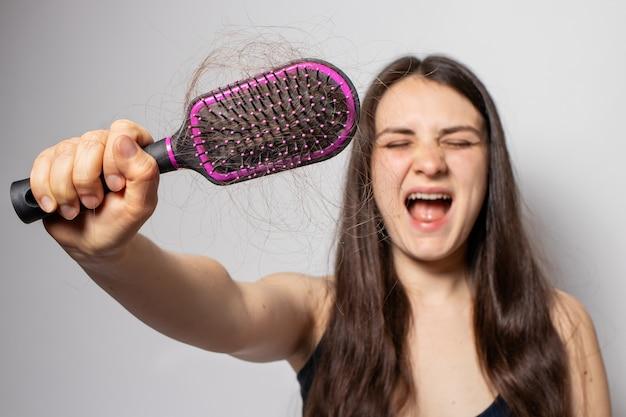 La niña sostiene un peine para cabello con cabello caído