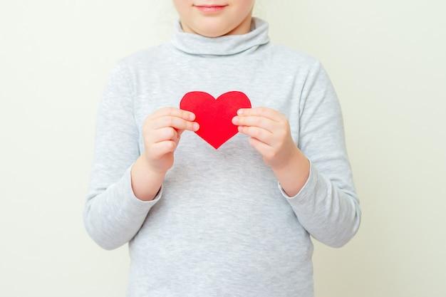 La niña sostiene el pequeño corazón rojo.