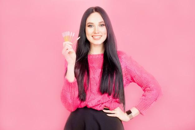 La niña sostiene pinceles de pestañas, una modelo con maquillaje, sobre un fondo rosa. concepto de maquillaje, rímel o extensión de pestañas master.