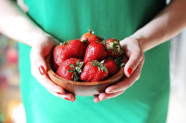 Niña sostiene un plato de fresa roja fresca