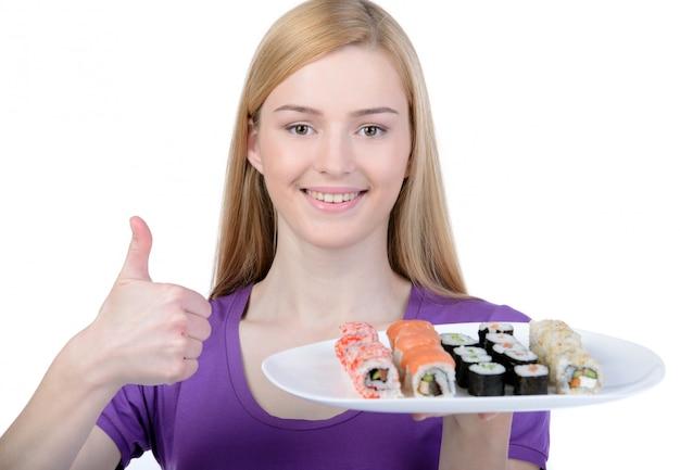 Una niña sostiene un plato de suma y muestra el gesto ok.