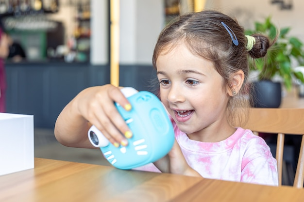 Una niña sostiene en sus manos una cámara digital de juguete azul para niños para la impresión instantánea de fotografías.