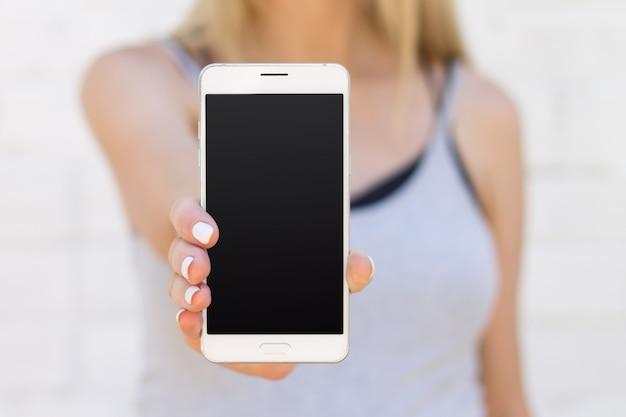 La niña sostiene un teléfono móvil con una pantalla negra en blanco en un brazo extendido de cerca