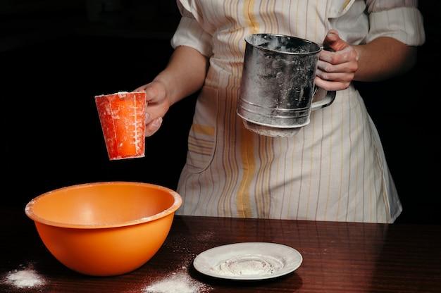 La niña sostiene un vaso de harina y un tamiz de harina. fondo negro. concepto.