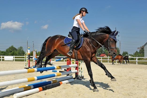 Niña en su caballo de bahía salta por encima de una barrera en la formación.