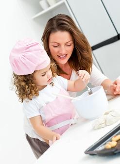 Niña con su hermosa madre cocinando juntos