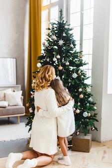Una niña con su madre cerca del árbol de navidad, el interior decorado para el año nuevo y navidad, familia y alegría, tradiciones