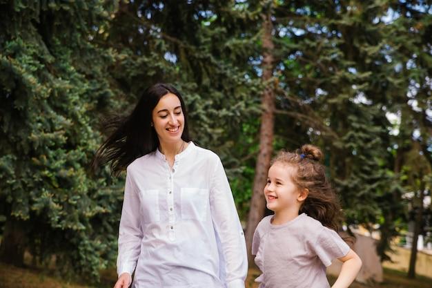 Una niña y su madre corren por la acera del parque. juego activo en la naturaleza.