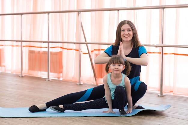 Una niña y su madre están haciendo deporte.