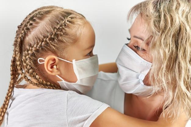 La niña y su madre con máscaras médicas blancas se abrazan y se miran