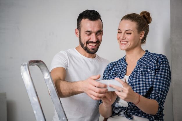 Niña y su novio miran fotos en la pantalla del teléfono. se toman un descanso de la renovación