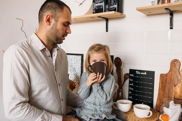 Niña con su padre en la cocina en casa. linda niña está sentada en la cocina con una taza de té.
